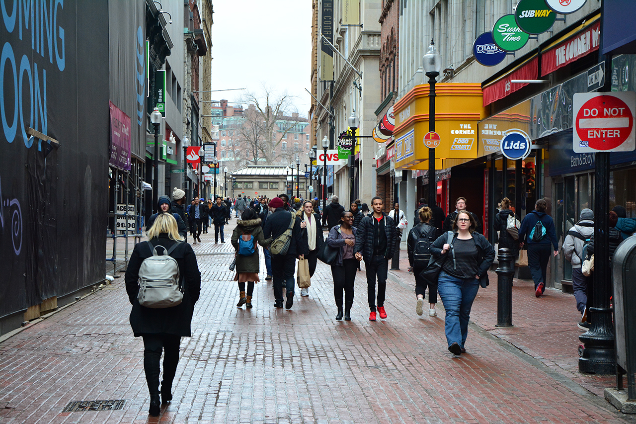 People walk in multiple directions down a narrow cobblestone street in Downtown Crossing, past rows of shops.