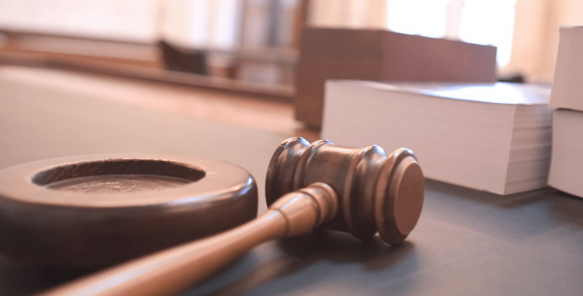 this stock image shows a gavel resting on a judge's bench in a courtroom
