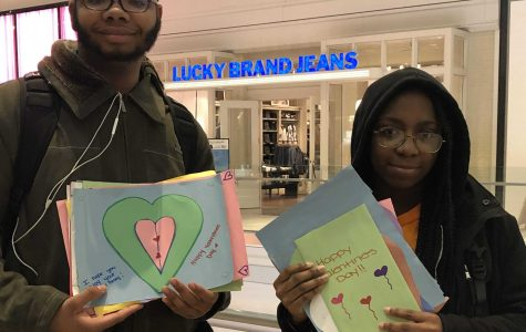 Young hands out Valentine's Day cards to strangers in the Copley Place Mall. Young is a member of Everyday Boston.