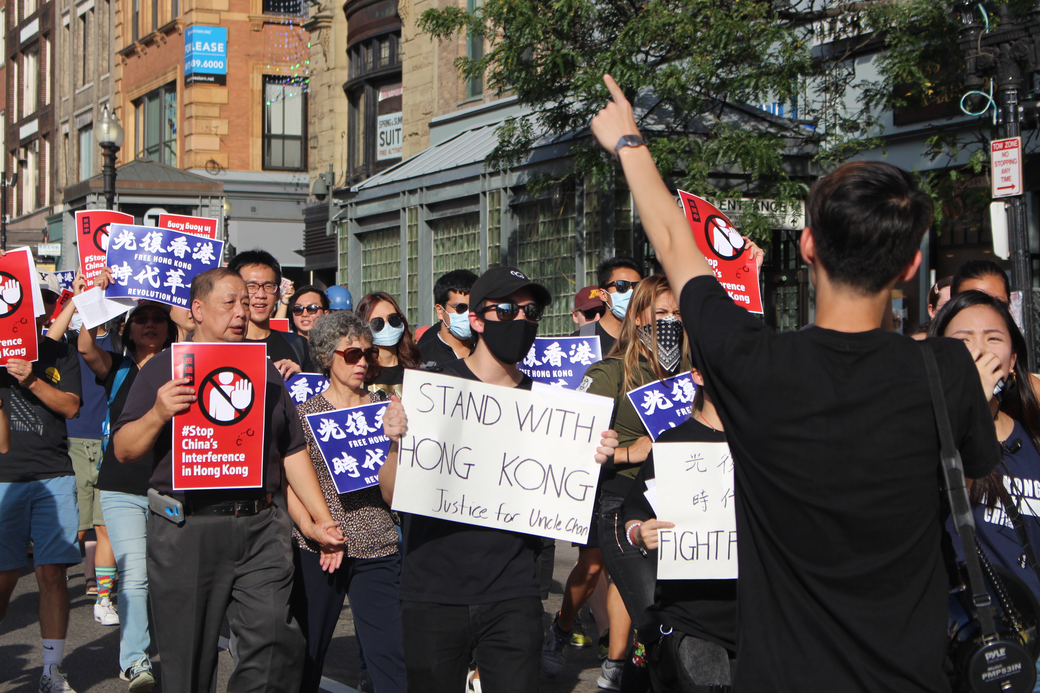 Marchers traveled down Boston's streets carrying banners and wearing masks to hide their identity. Photo by Lex Weaver.