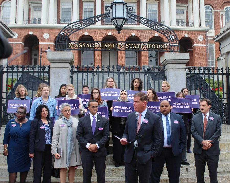 (From left to right) Mayors Yvonne Spicer of Framingham, Donna Holaday of Newburyport, Nicole LaChapelle of Easthampton, Joseph Curtatone of Somerville, Martin Walsh of Boston, Daniel Rivera of Lawrence and Marc McGovern of Cambridge, all stood and some spoke in support of the act that would protect and expand abortion rights and reproductive health care access across Massachusetts. Photo by Catherine McGloin.