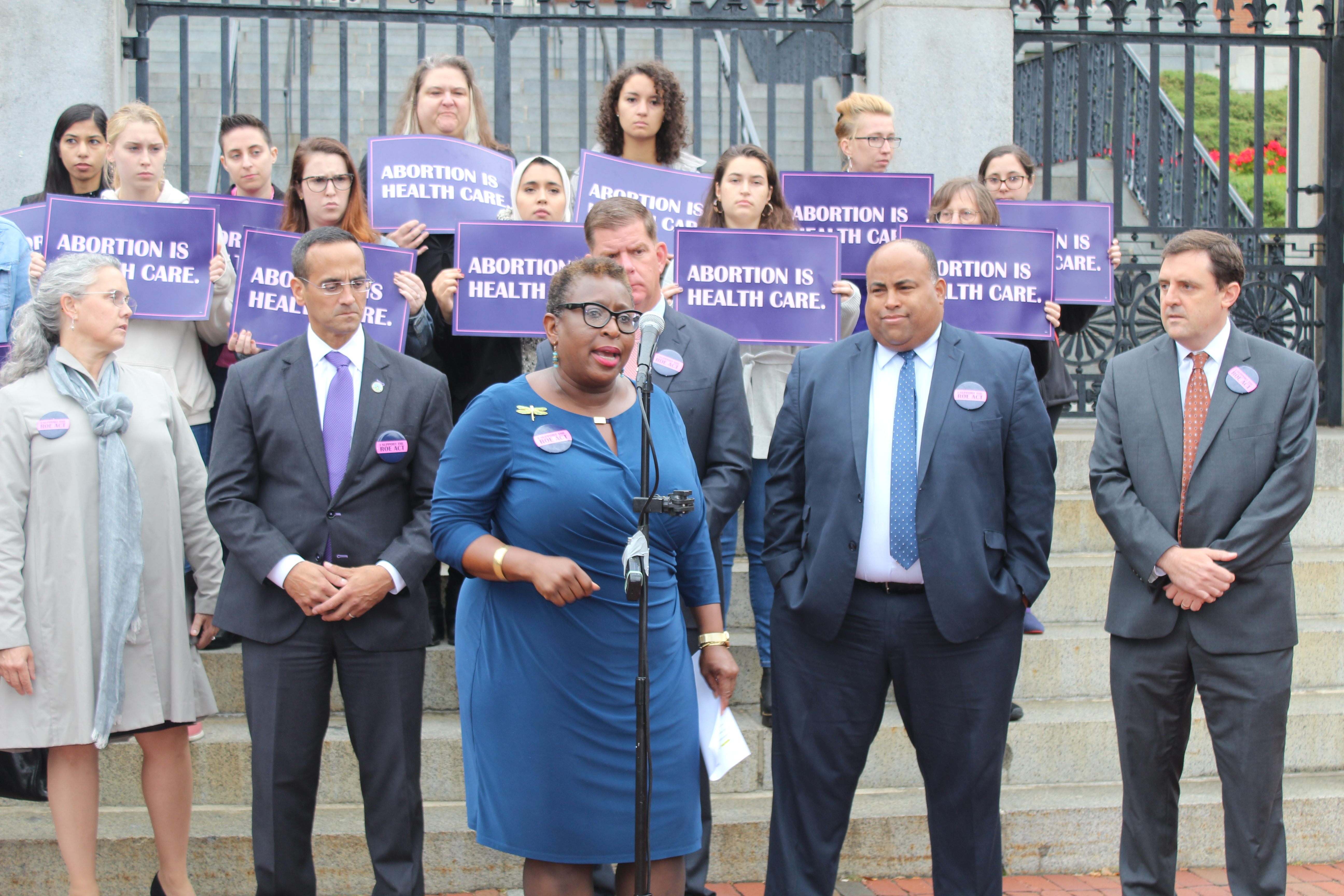 (From left to right) Mayors Nicole LaChapelle of Easthampton, Joseph Curtatone of Somerville, Martin Walsh of Boston, Daniel Rivera of Lawrence and Marc McGovern of Cambridge, stood behind Mayor Yvonne Spicer of Framingham while she spoke of the impact this bill would have on the health care received by women of color in Massachusetts. Photo by Catherine McGloin.
