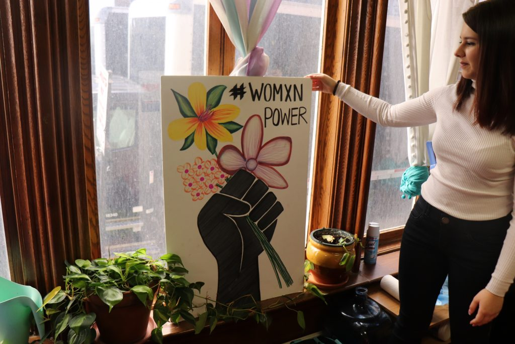 Do Vale displays a sign that they carried in the Womens March. Photo by Eileen O'Grady.