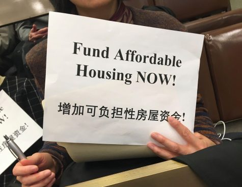 "Silent protestors in the crowd held signs that said ""Fund Affordable Housing NOW!"" Photo by Joseph Handel."