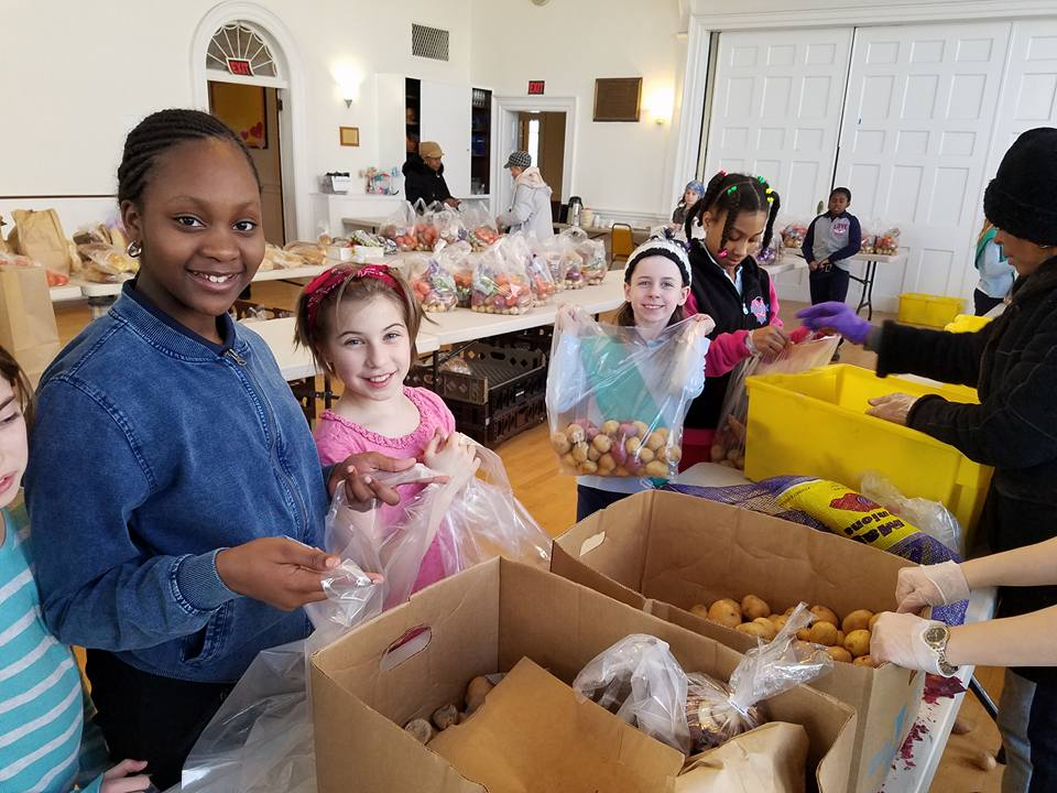 Girl Scouts help people buy groceries at one of Fair Foods' two-dollar-a-bag food sites. Photo by Gene Thorpe.