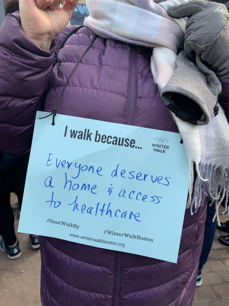 Walkers in Copley Square wear signs explaining their motivation to join the Winter Walk. Photo by Maria Aguirre.