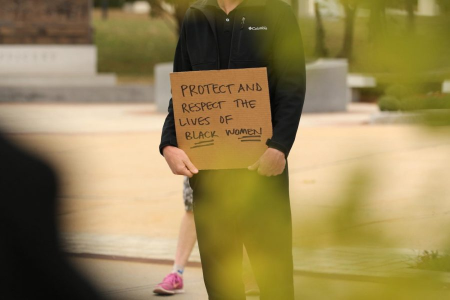 "A protester holding a sign saying ""Protect and respect the lives of Black women."""