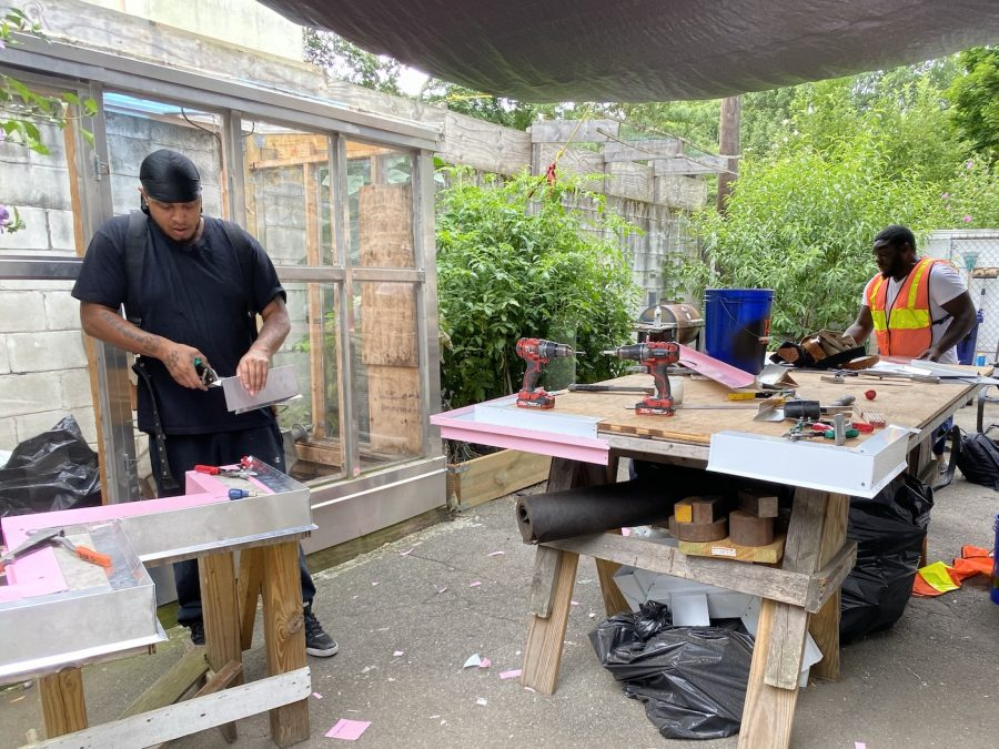 Two of The People's Academy's trainees working in the backyard workshop. Photo: Huilin Li.