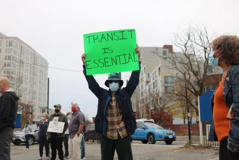 "A protester holding up a sign ""Transit is essential"" at the Heath Street station protest against the MBTA service cuts"