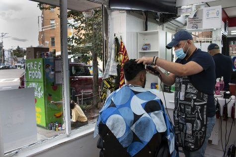 "Despite the pandemic, barbers are still cutting and styling at D'Friends Barber Shop in Jamaica Plain. The Community Fridge can be seen from the inside of the shop with Northeastern student Talja Ketchum painting vibrant rainbows and flowers onto its exterior. The barbers are enthusiastic about the new initiative right outside their door. ""My best friend gets a haircut at this barbershop all the time, so he put me in contact with the owner,"" said Josiel Gonzalez, a co-founder and main organizer for the JP fridge. Jay Valeria, 24, has been a barber at D'Friends for three years now. ""There's a lack of love and warmness [in the world],"" explained Valeria. ""I feel like this promotes love."""