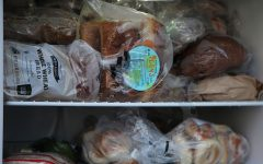 The fridge's freezer is stocked with a wide array of baked goods — bagels, rolls and loaves of bread.
