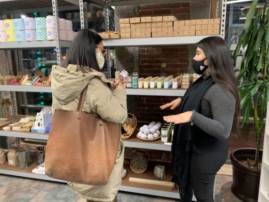 UVIDA shop owner Maria Camila Vasco (right) explains one of her deodorant products to a customer at the North End store.